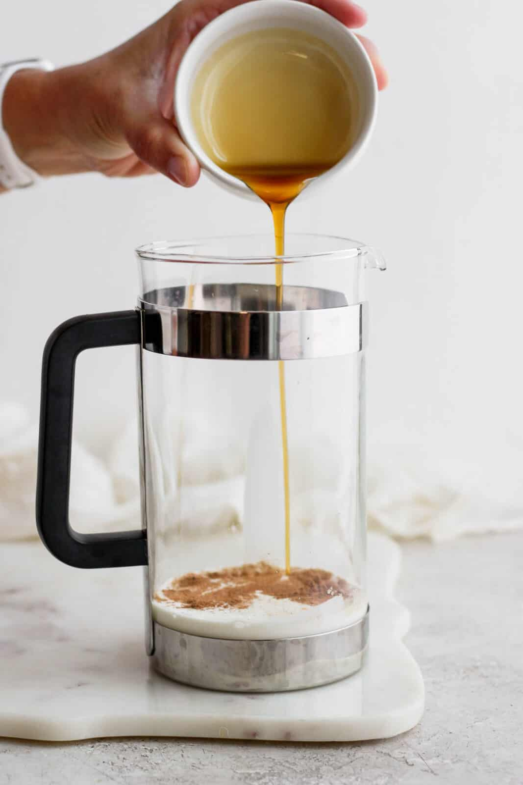 Someone pouring maple syrup into a French press.