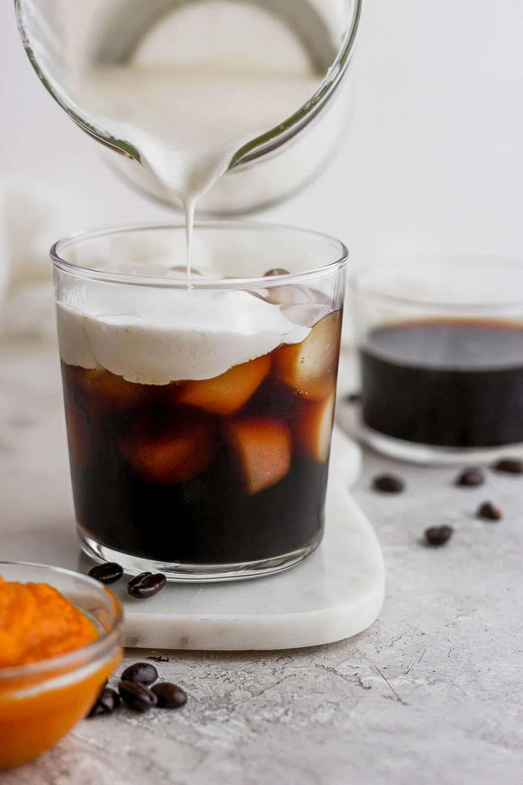Someone pouring pumpkin cream over a glass of cold brew coffee.
