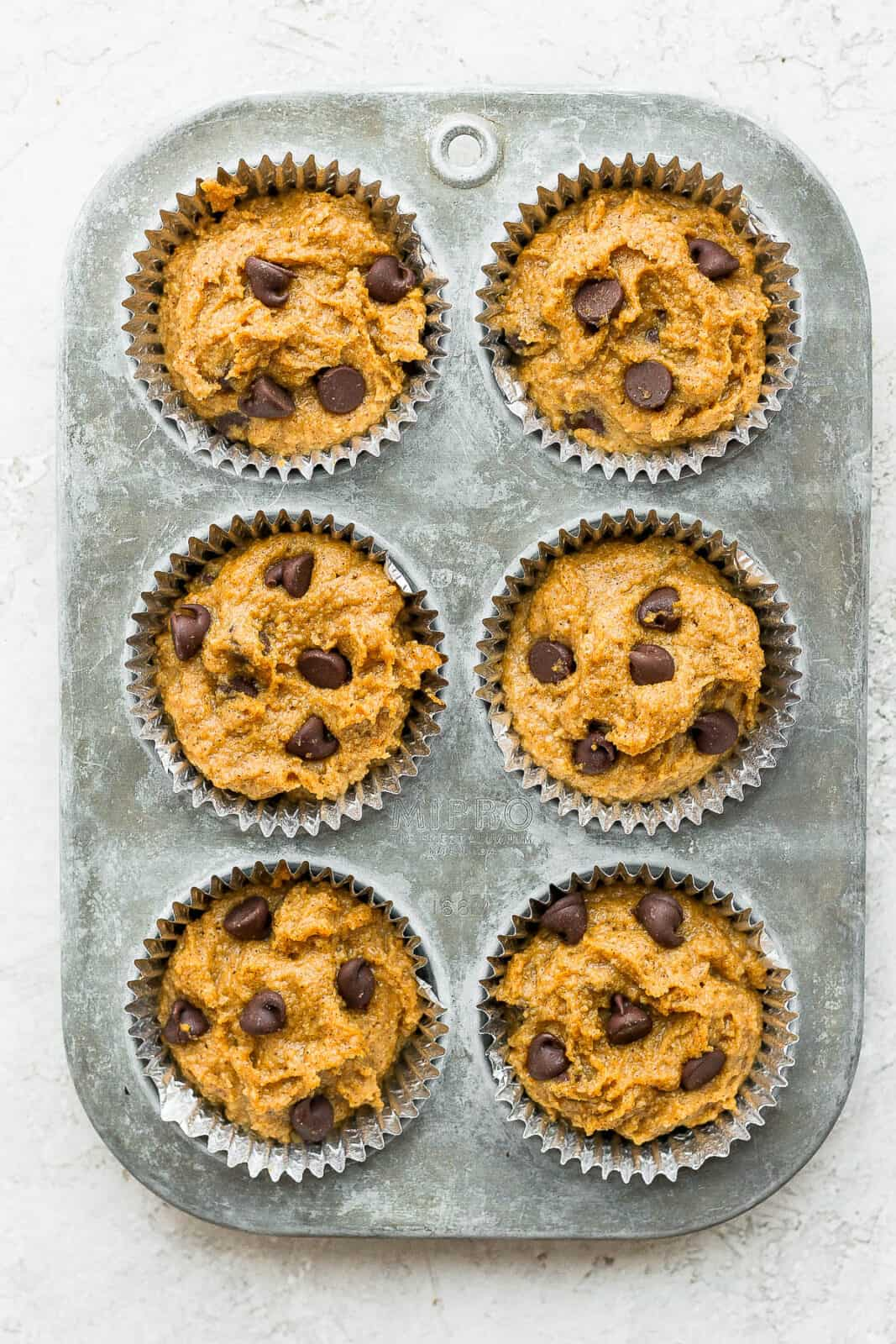 Pumpkin muffins batter in a muffin tin before baking.