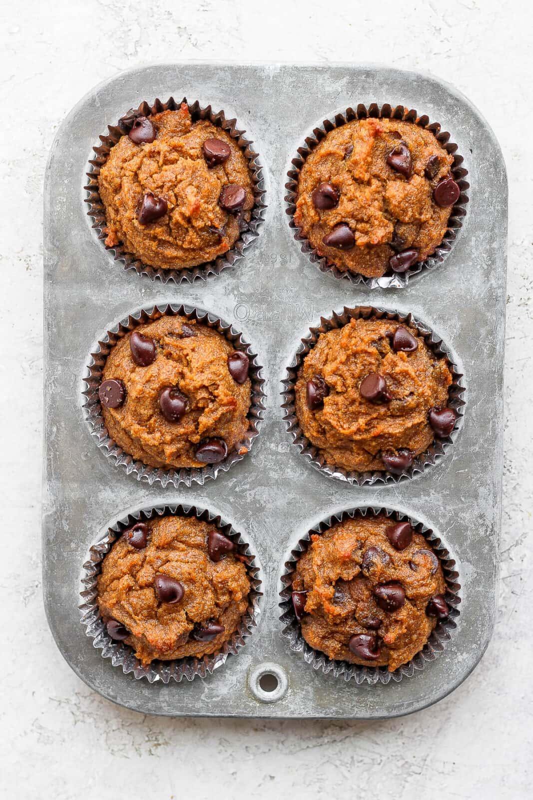 Pumpkin muffins in a muffin tin after baking.