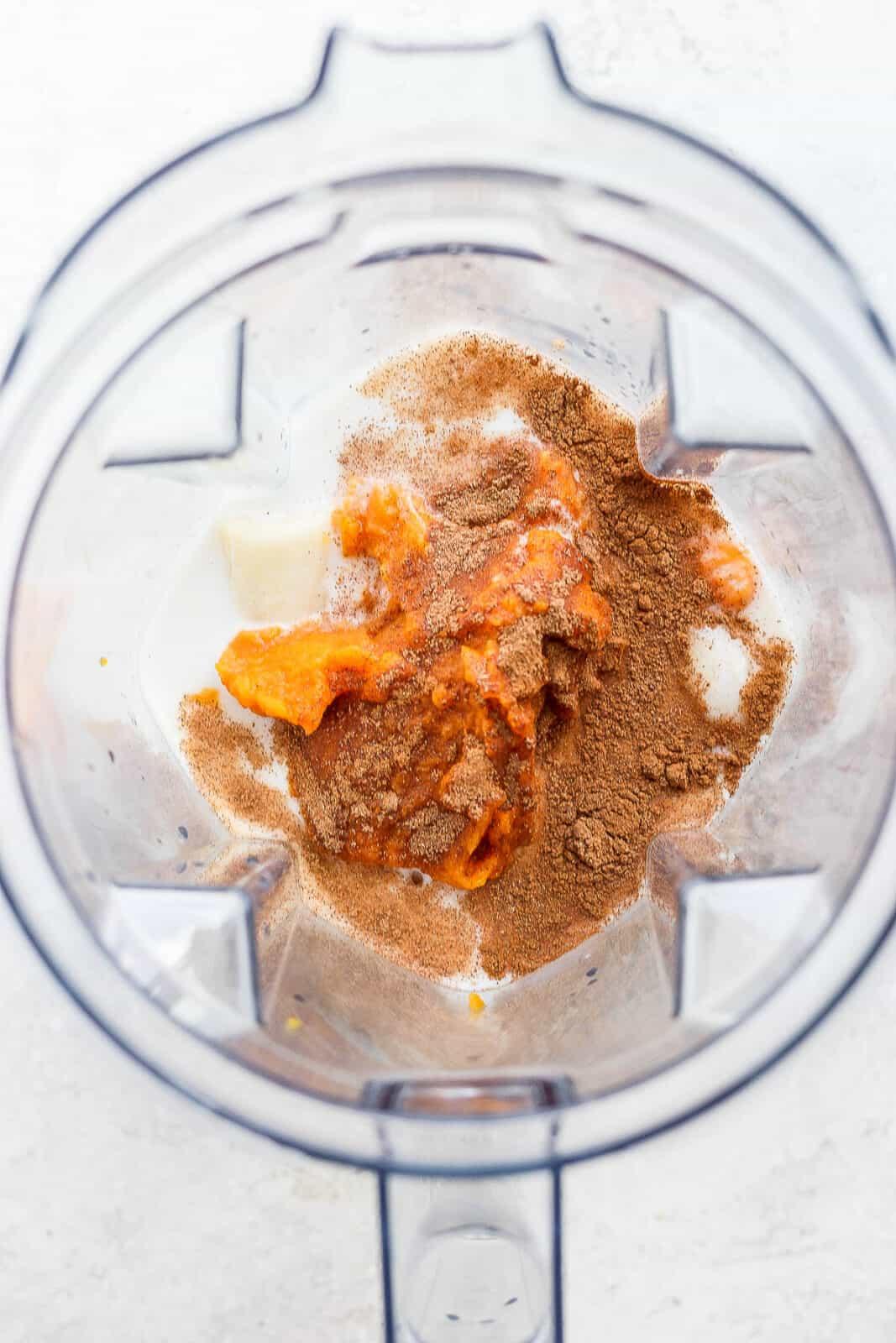Pumpkin smoothie ingredients in a blender.