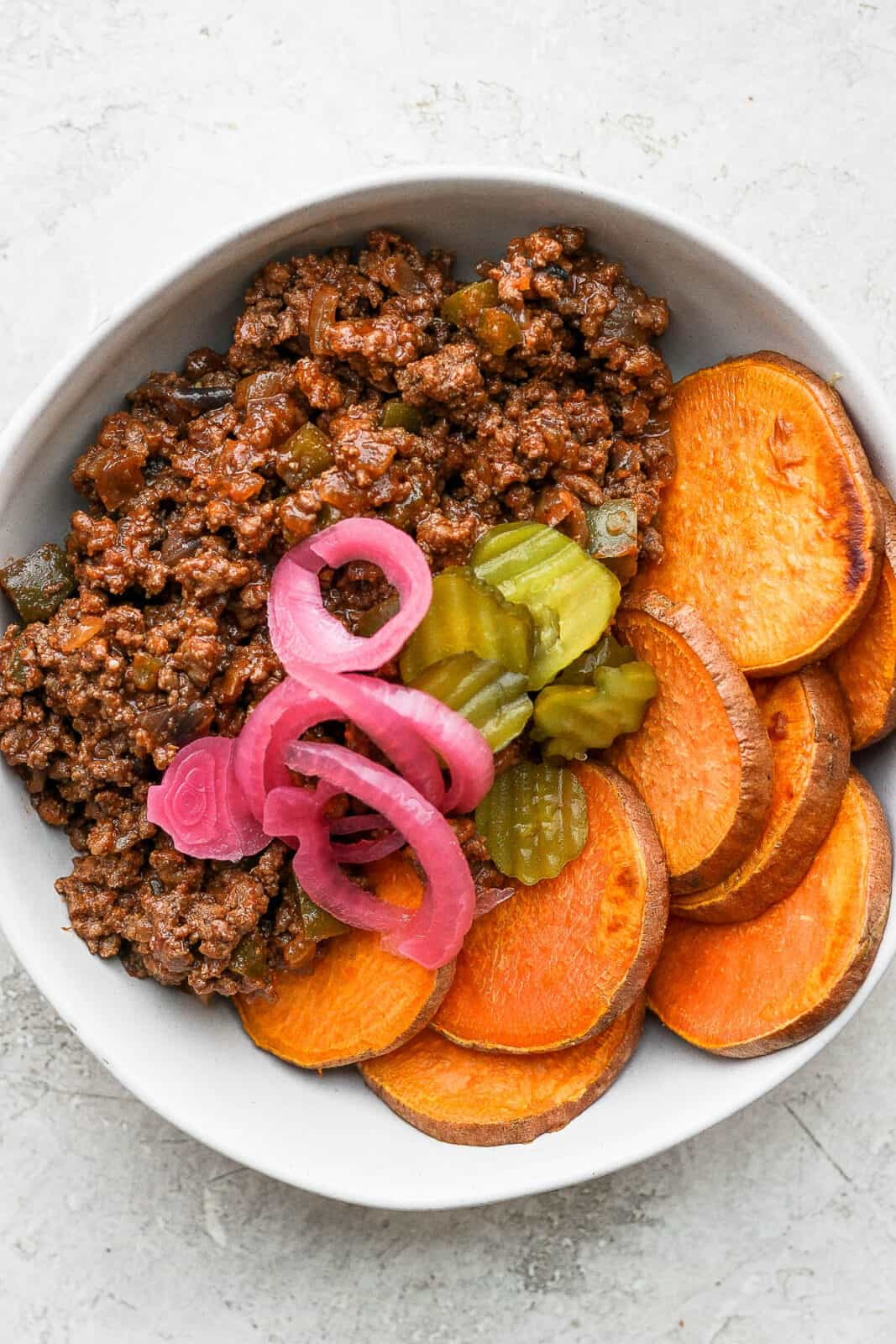 A sloppy joe bowl with pickles and pickled red onion on top.