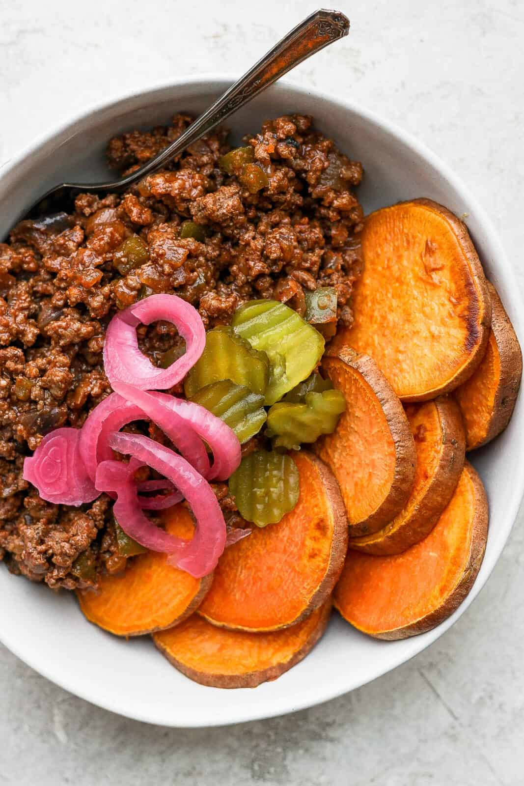 A sloppy joe with pickled onions and burger pickles on top.