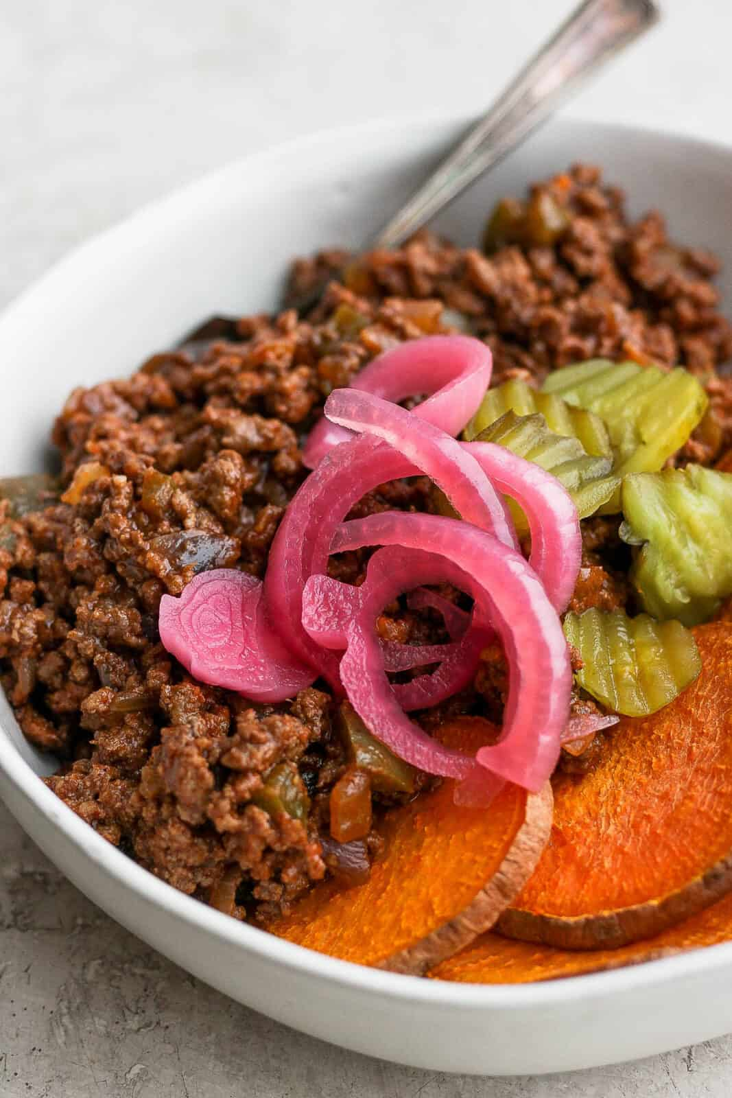 A sloppy joe bowl with pickled red onions and burger pickles on top.