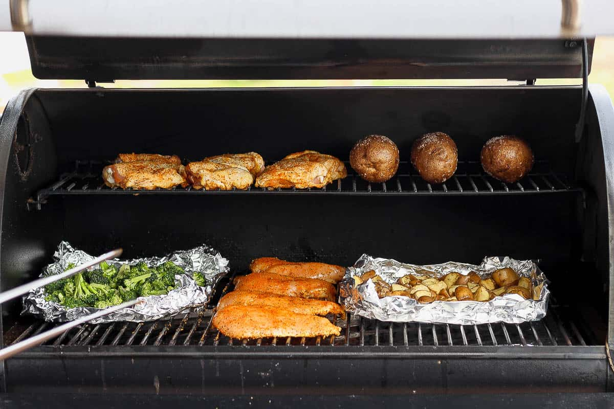 A smoker filled with smoked chicken breasts, broccoli, potatoes and chicken thighs.