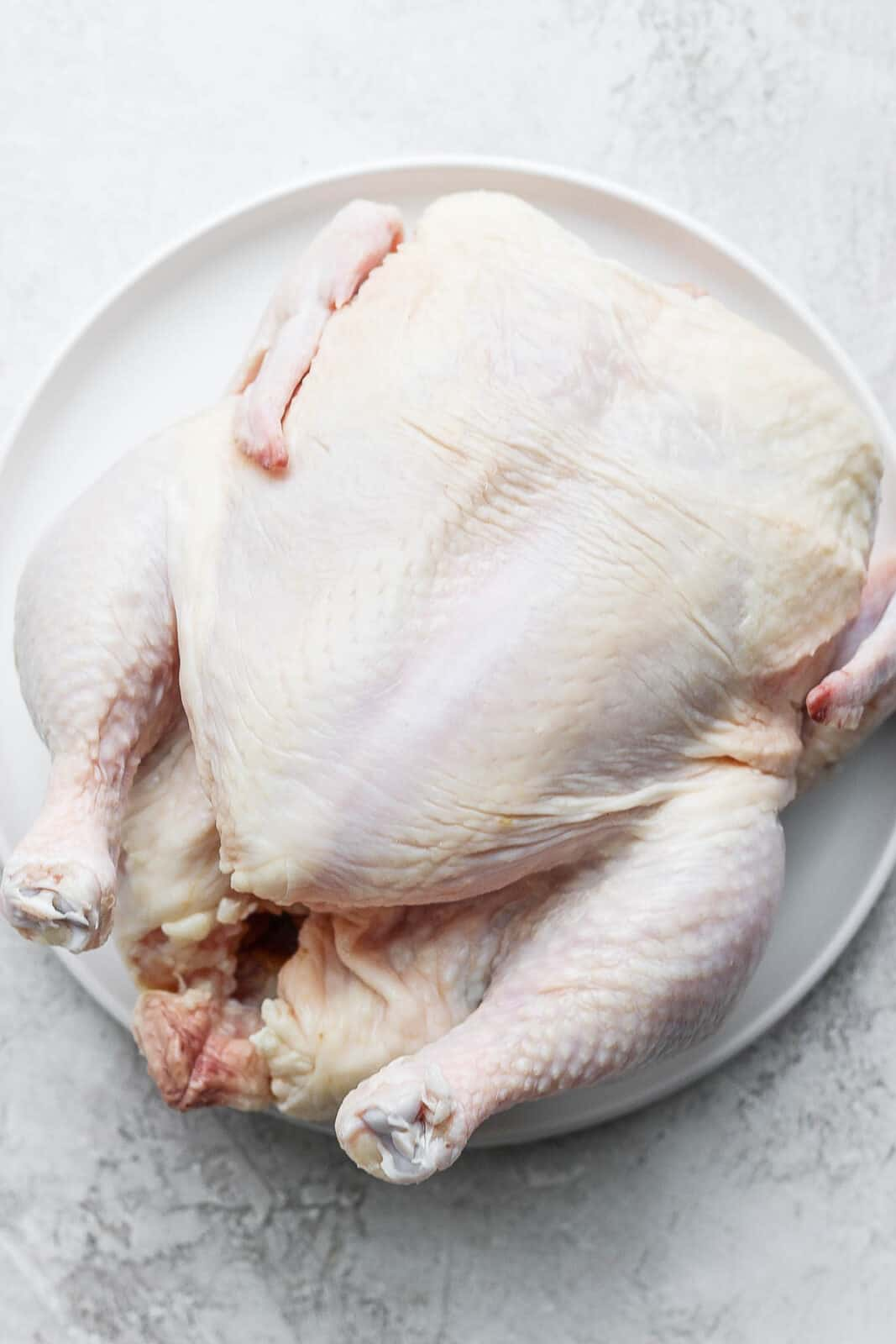 A whole, raw chicken on a plate.