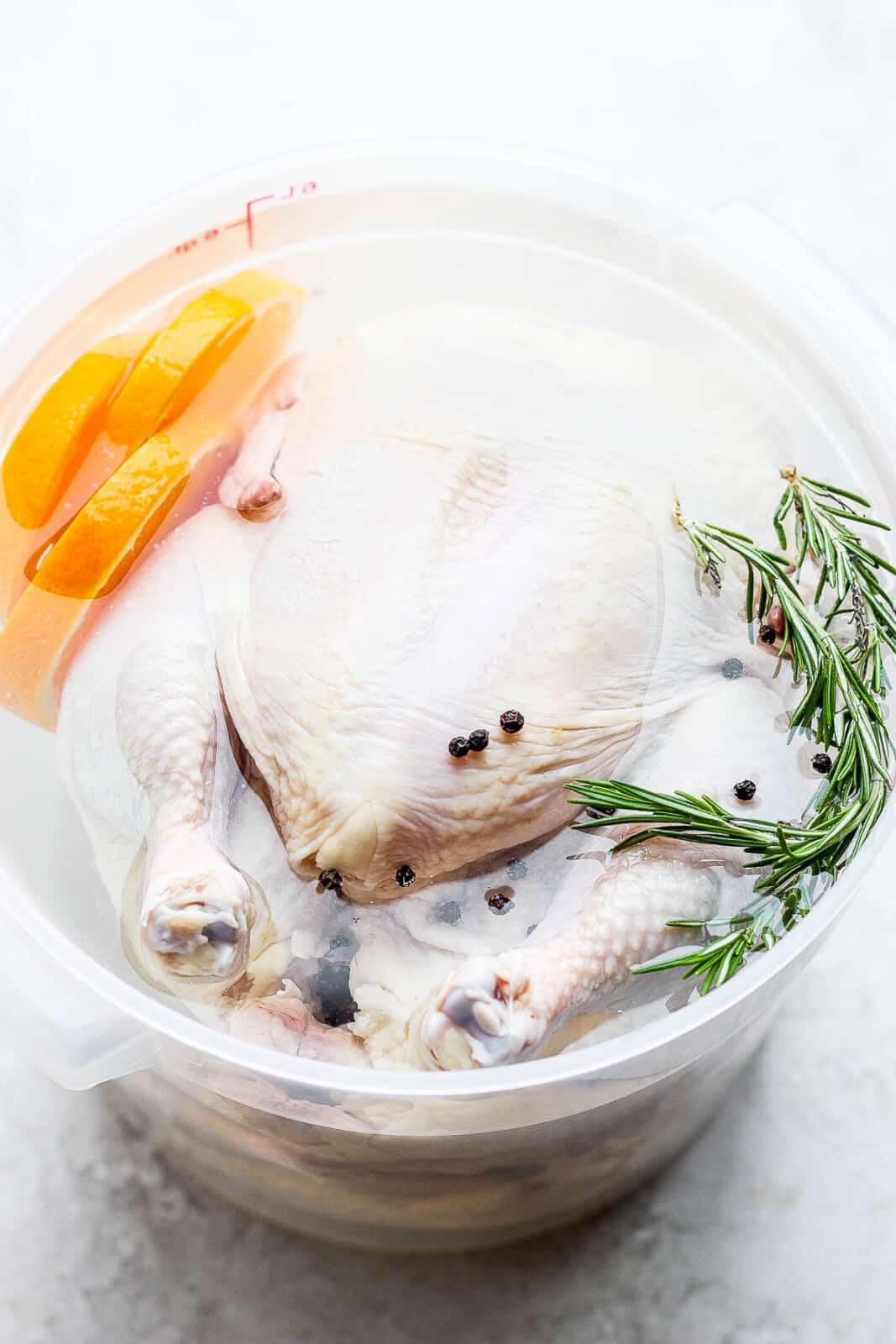 A food grade bucket with a whole chicken inside covered with a brine.