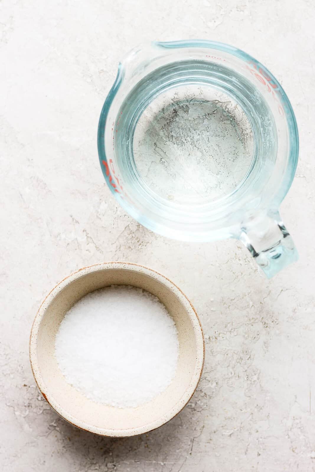 A bowl of kosher salt and measuring cup of water.