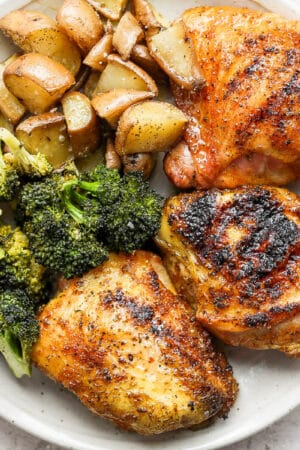 Plate of smoked chicken thighs, broccoli and potatoes.