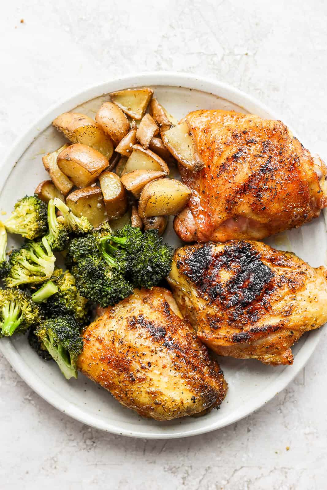 A plate of smoked chicken thighs, smoked broccoli and smoked potatoes.