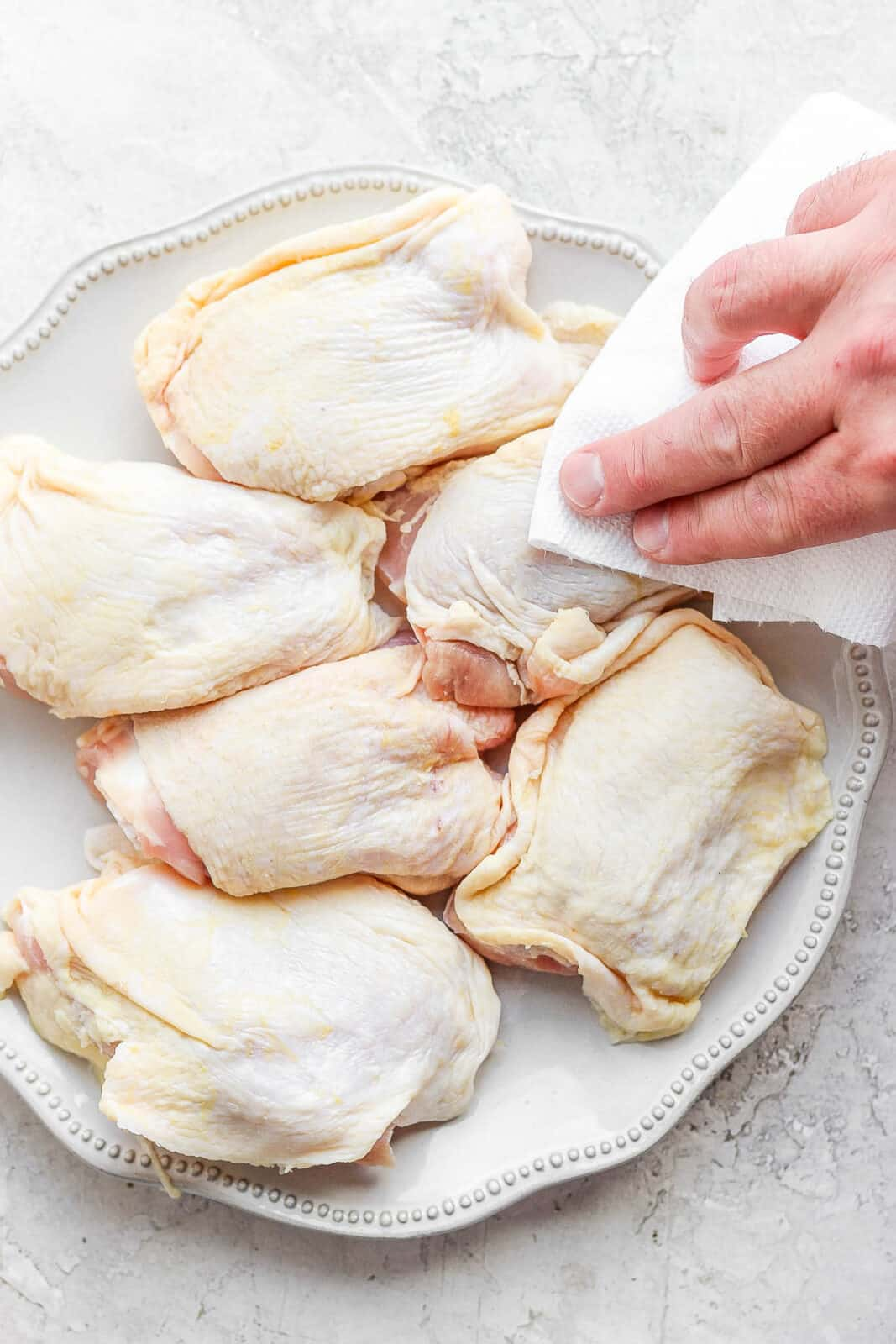 A plate of chicken thighs with someone patting them dry with a clean paper towel.