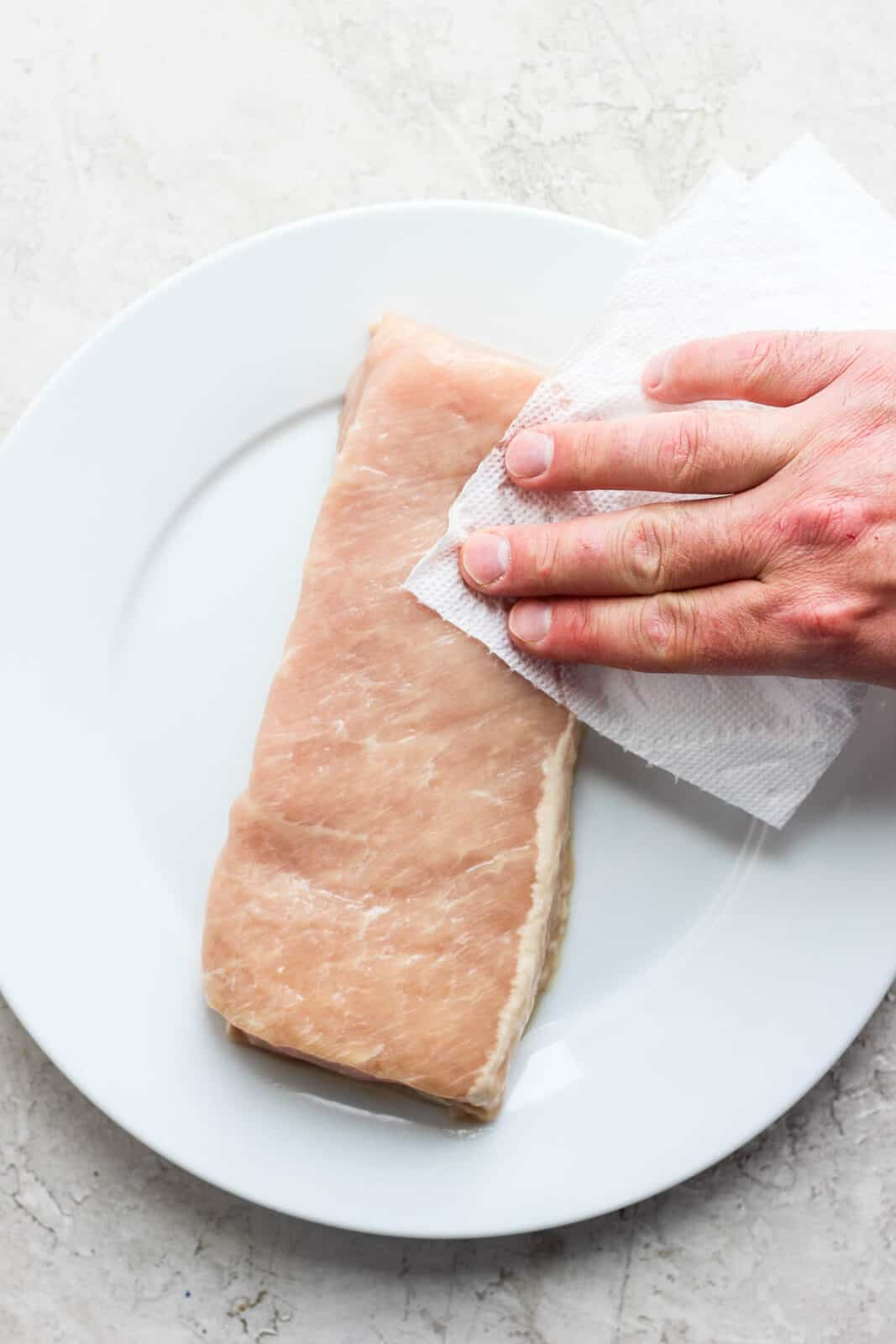 Someone patting dry a pork loin with a clean paper towel.