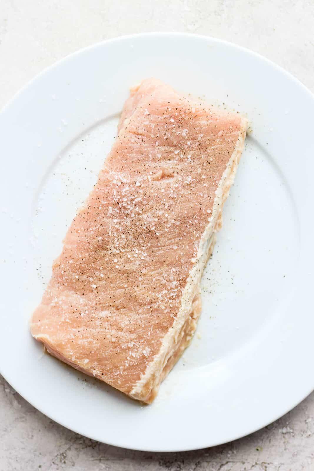 A raw pork loin seasoned with salt and pepper.