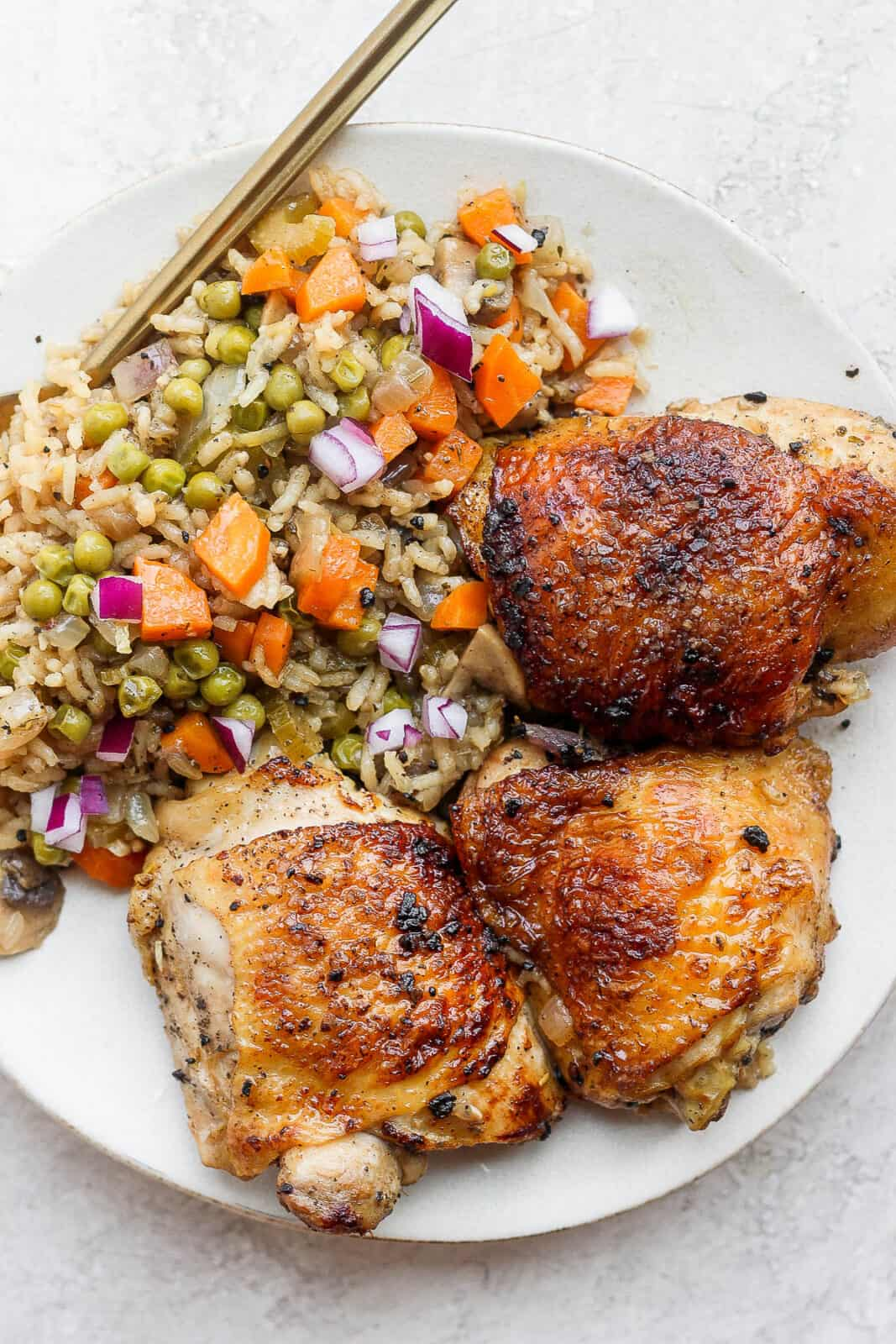 Baked chicken and rice on a plate.
