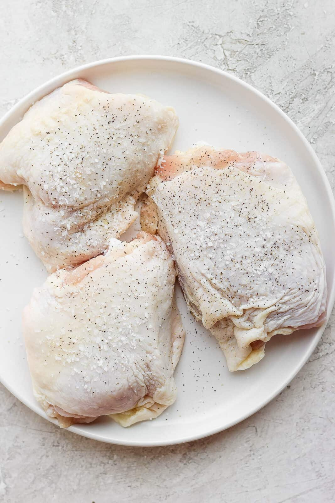 Raw chicken thighs seasoned and on a plate.