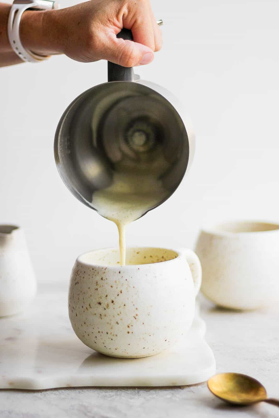 Pouring frothed pistachio milk on top of coffee in a mug.