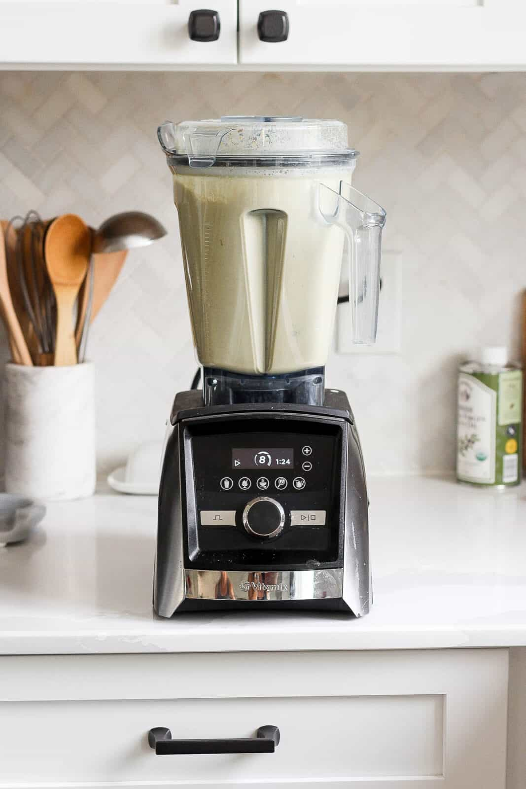 Pistachios and water being blended on high in a blender.